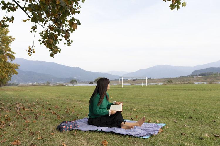 Man sitting on field against sky