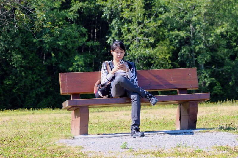 Young woman listening music through smart phone while sitting on bench against trees at park