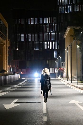 Rear view of woman walking on illuminated road at night