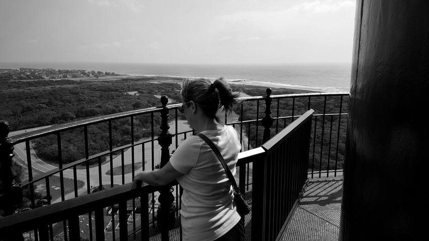 Bnw_scraps Of Sky Bnw_friday_eyeemchallenge Lighthouse Water Sea Standing Women Railing Beach Sky Horizon Over Water Surf Coastline Shore Ocean Seashore
