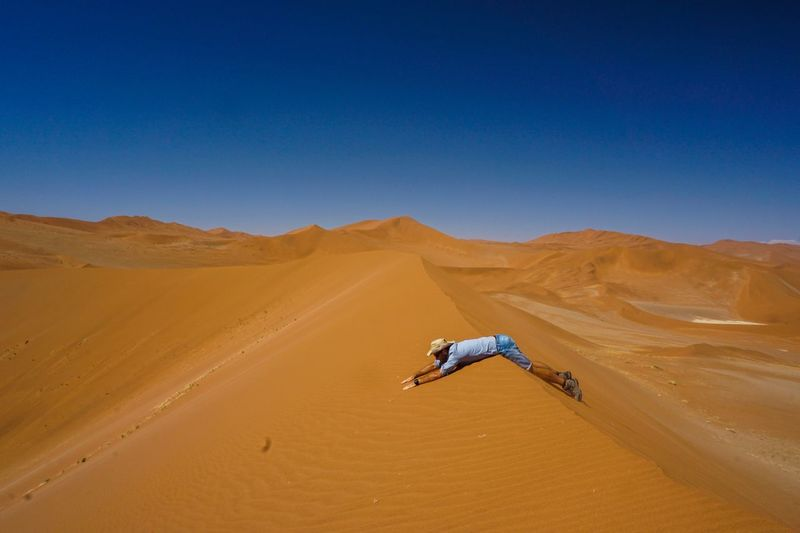 Side view of man lying on sand dune in desert against clear blue sky