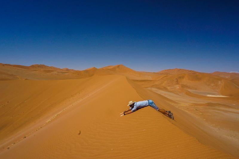Side view of man lying on sand dune in desert against clear blue sky