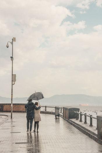 Rear view of couple with umbrella on street during rainy season