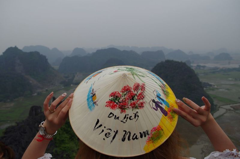 Rear view of woman holding asian style conical hat against mountains