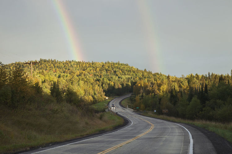 Double rainbow above curving road and wooded hills in northern Minnesota during autumn Autumn Dramatic Sky Hills Minnesota Road Travel Trees USA Aspen Beauty In Nature Birch Car Curve Double Rainbow Forest Highway North Pine Tree Rainbow Road Sky Sundown Sunlight And Shadow Truck Two