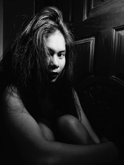 Close-Up Portrait Of Young Woman Sitting In Darkroom