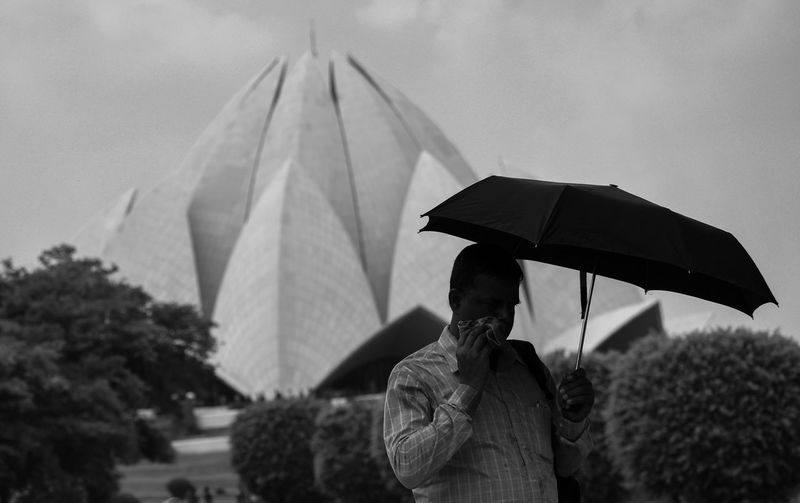 Rear view of man standing with umbrella against sky