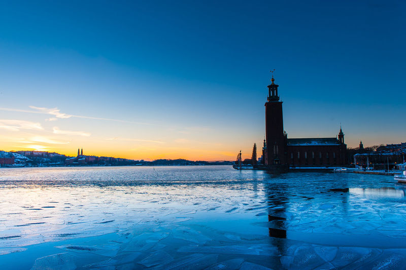 Frozen Riddarfjarden With Stockholm City Hall Against Sky During Sunset