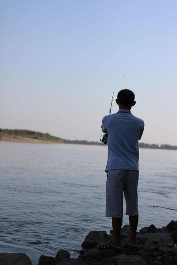 Rear view of man fishing in lake during sunset