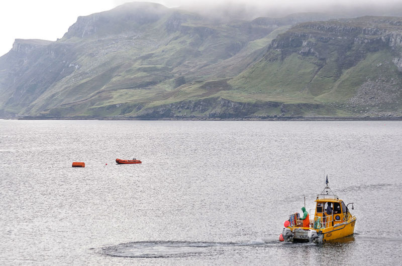 Fishing boat heads out from the harbour at Portree, Isle of Skye Scotland Day Fishing Fishing Boat Highlands Of Scotland Mist Mode Of Transportation Mountain Nautical Vessel Non-urban Scene Sea Transportation Water
