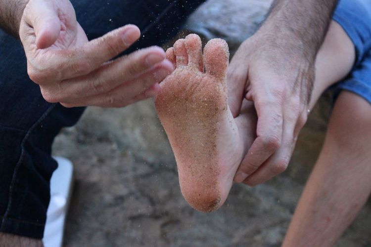 Man cleaning boy's sandy feet