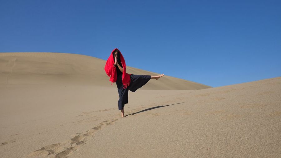 Full length of woman standing at desert against clear blue sky on sunny day