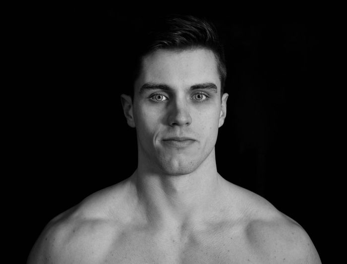 Portrait of shirtless young man against black background