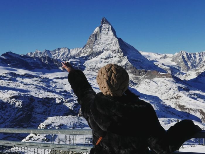 Rear view of woman gesturing towards snowcapped mountain against sky