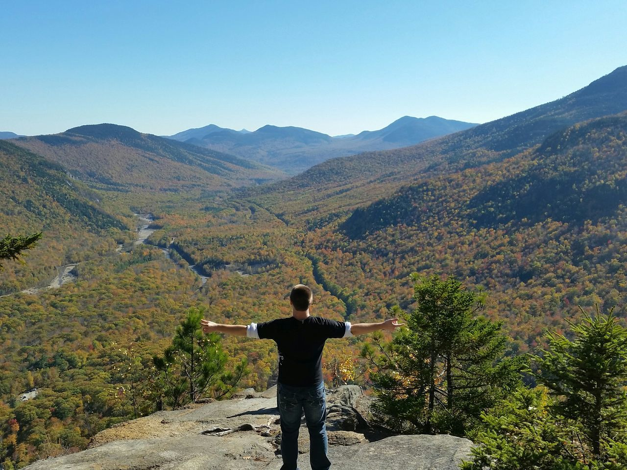 Rear View Of Man Standing On Rock With Arms Outstretched By Mountains Against Clear Blue Sky
