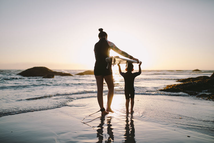 Silhouette mother holding surfboard on son head at beach during sunset
