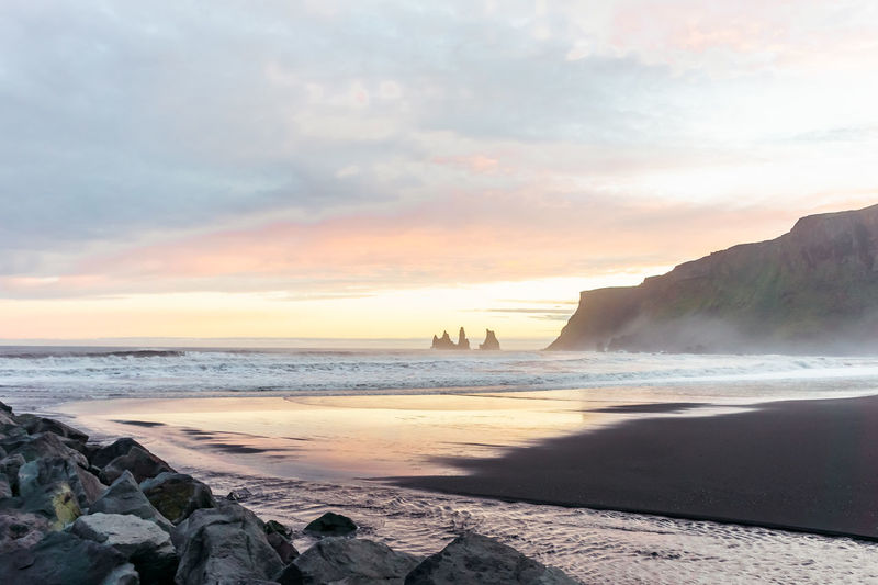 Famous Reynisdrangar rock formations at black Reynisfjara Beach. Coast of the Atlantic ocean near Vik, southern Iceland. Reflection Rock Beach Beauty In Nature Black Sand Beach Cloud - Sky Day Horizon Over Water Icland Icland Trip Nature No People Outdoors Rock - Object Sand Scenics Sea Shore Sky Sunset Tranquil Scene Tranquility Vik Water Wave