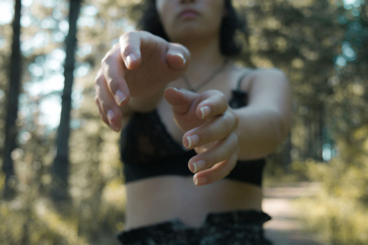 Midsection of young woman gesturing while standing in forest