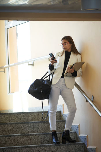 Young businesswoman using smartphone while standing