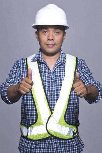 Portrait of young asian man engineer Asian  Engeneering Gray Background Indoors  Looking At Camera One Person Portrait Real People Smiling Standing Studio Shot Young Adult