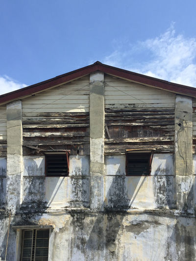 Low angle view of abandoned house against sky