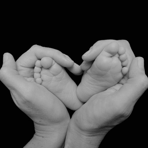 Close-Up Of Hands Holding Baby's Feet