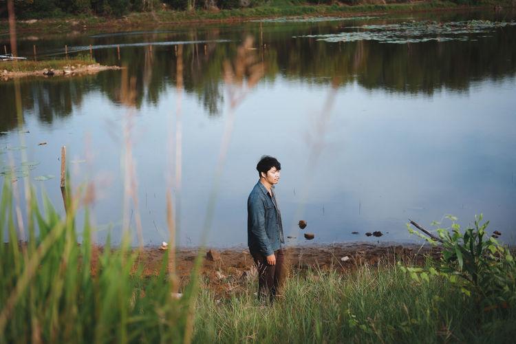 Young man standing at lake
