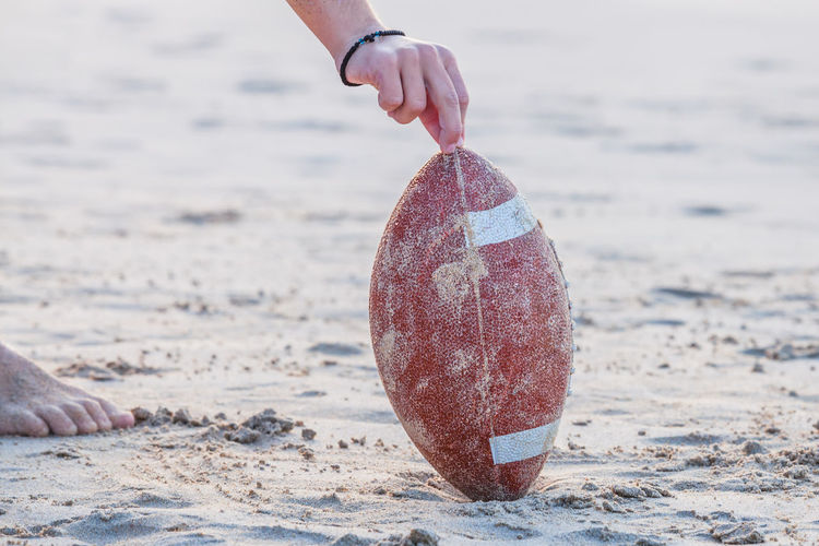Cropped Hand Of Man Holding Rugby Ball On Sand At Beach