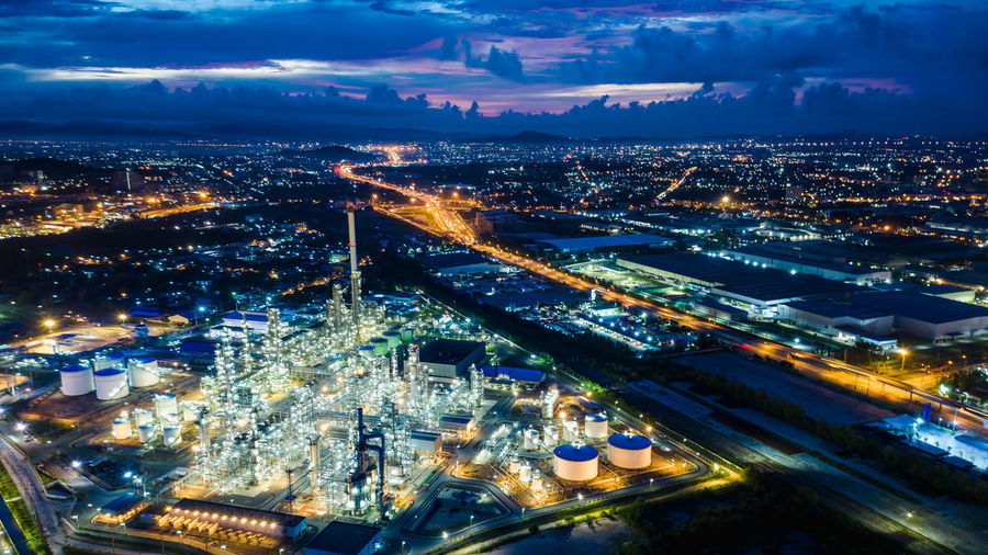 Refinery zone at night and lighting cityscape with blue sky background aerial view from drone