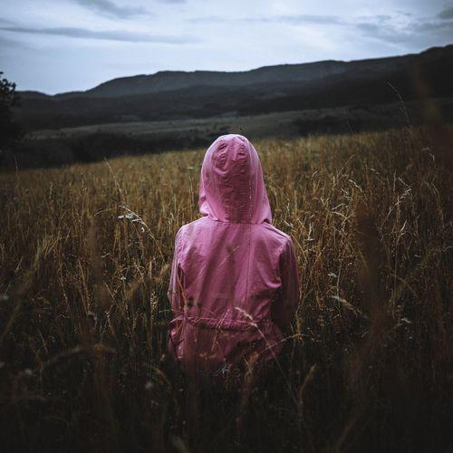 Rear view of girl wearing raincoat standing in field