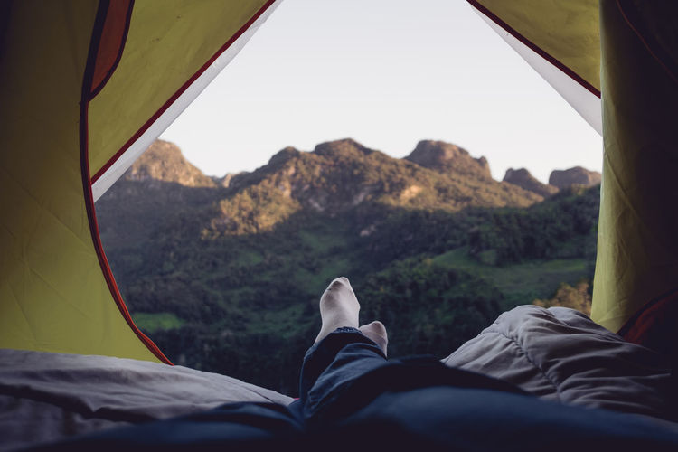 Low section of man relaxing in tent