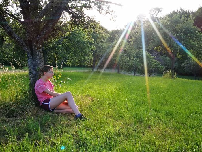 Side view of teenage girl sitting by tree on grassy field