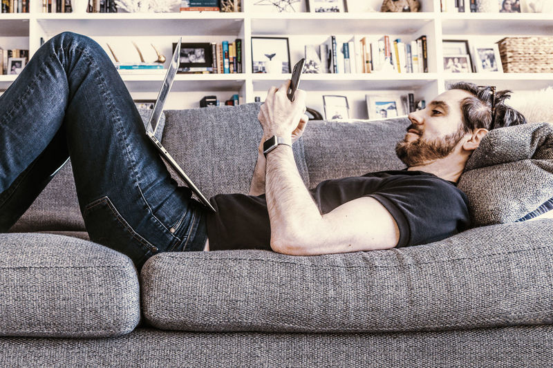 Man working with laptop computer and smart phone while laying on home sofa couch.