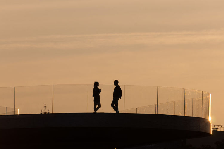 Silhouette people standing by railing against sky during sunset