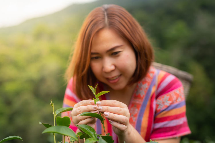 Portrait of beautiful woman holding fresh plant