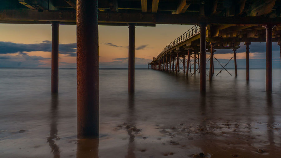 Sea Below Pier Against Sky During Sunset