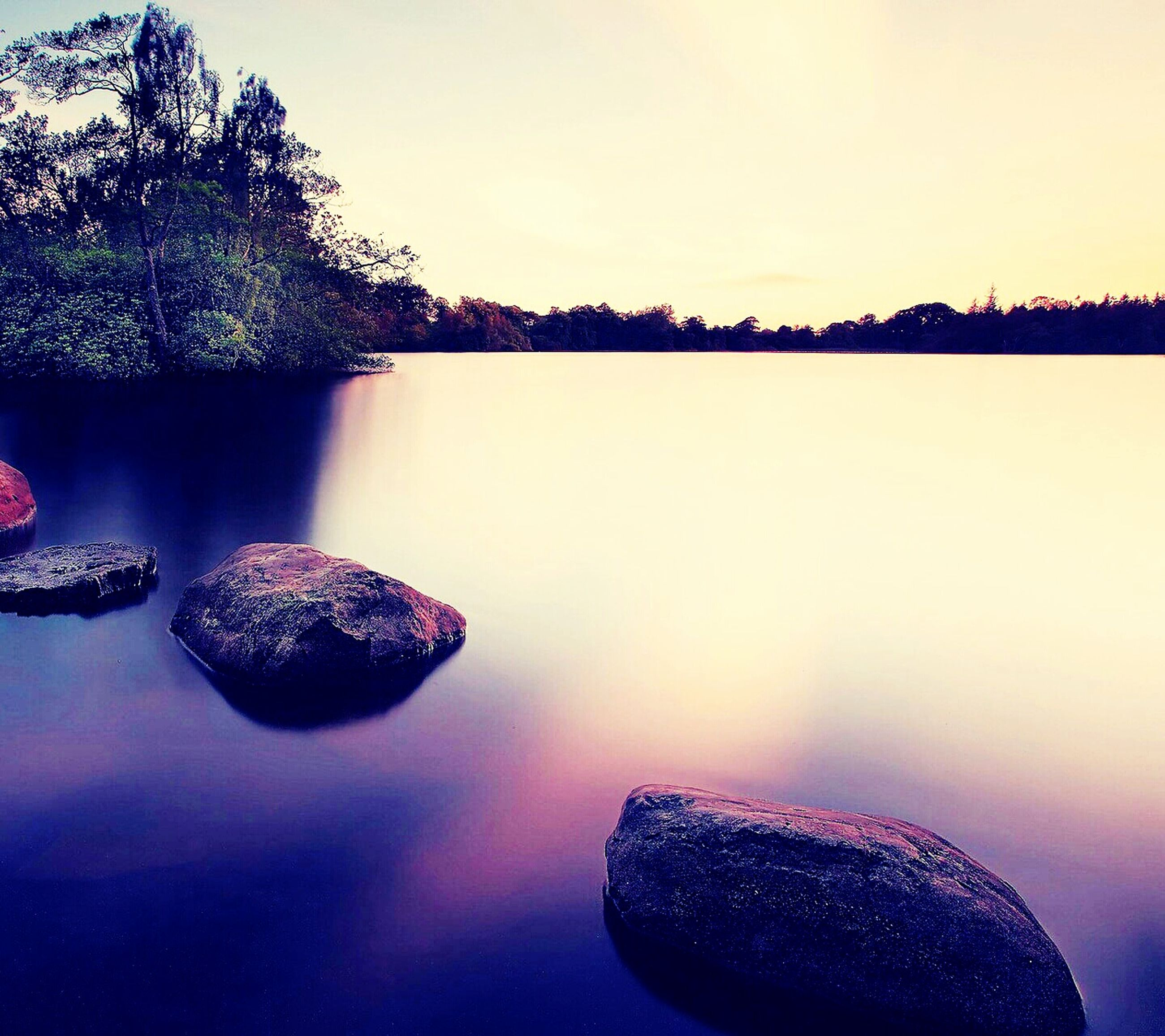 water, reflection, tranquility, tranquil scene, beauty in nature, scenics, nature, clear sky, rock - object, lake, waterfront, stone - object, tree, idyllic, sky, copy space, no people, sunset, standing water, outdoors
