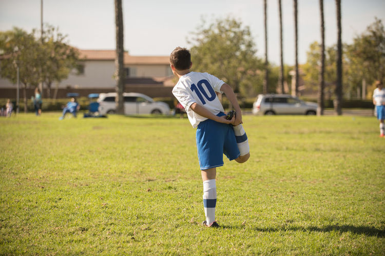 Full length of boy playing soccer on field