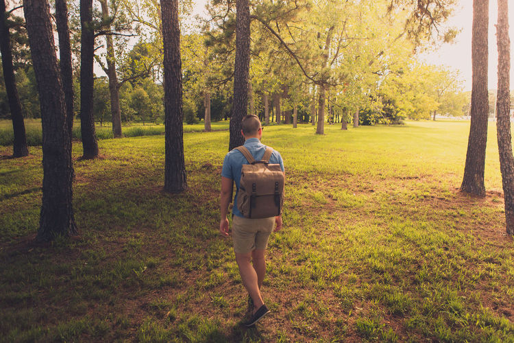 Rear View Of Man Hiking On Grassy Field