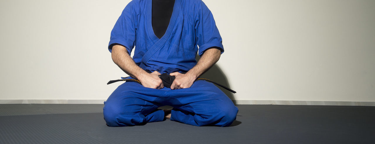 Low Section Of Male Judo Sitting On Floor Against Wall