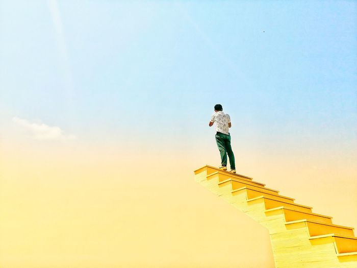 Low angle view of person standing on staircase against sky