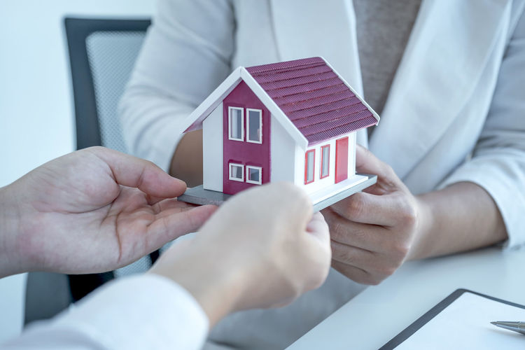 Close-up of man holding hands by house against building