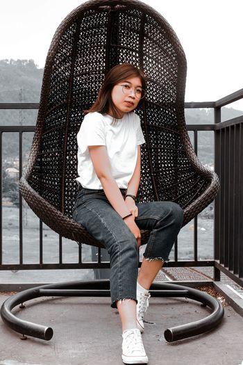 Full length portrait of smiling woman sitting on railing