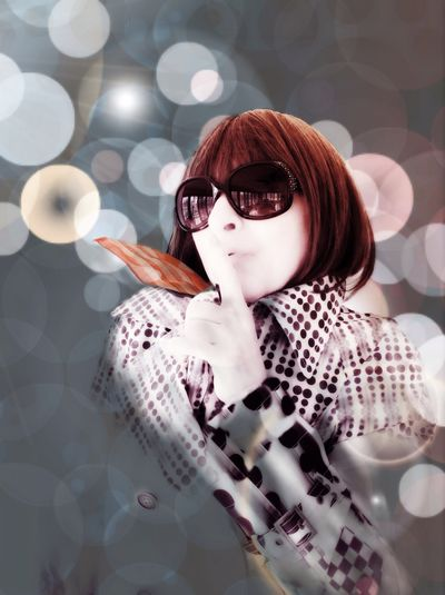 Portrait of trendy woman making silent gesture in studio