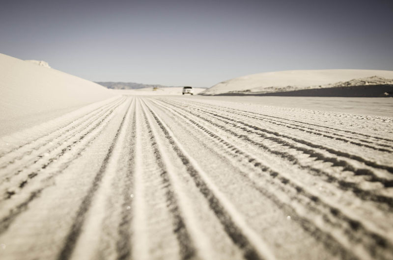 Tire Tracks On Snowy Landscape Against Clear Sky