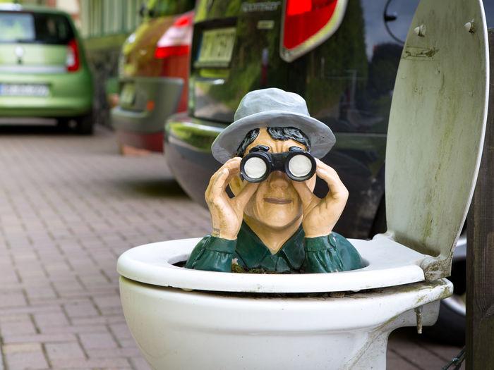 Sculpture with binoculars in toilet bowl on footpath