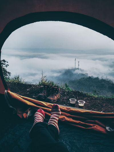 Low section on person in tent against sky during foggy weather
