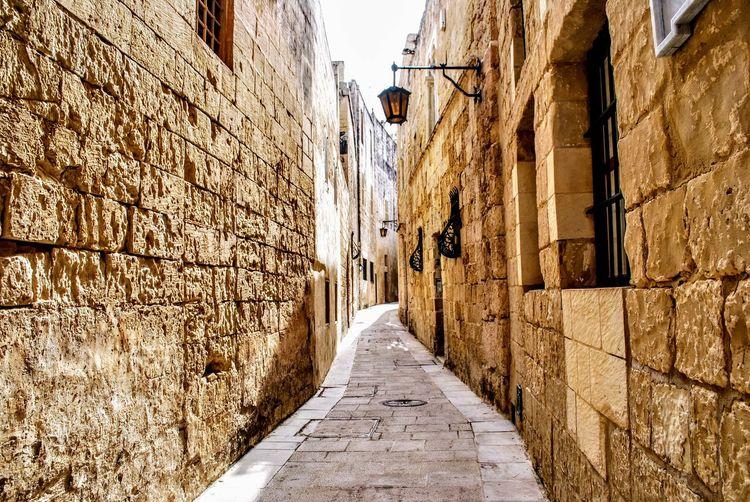 Narrow Alley Amidst Buildings Against Sky