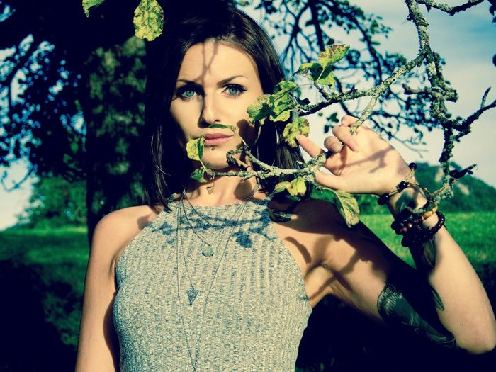 Portrait of beautiful woman standing by tree on sunny day