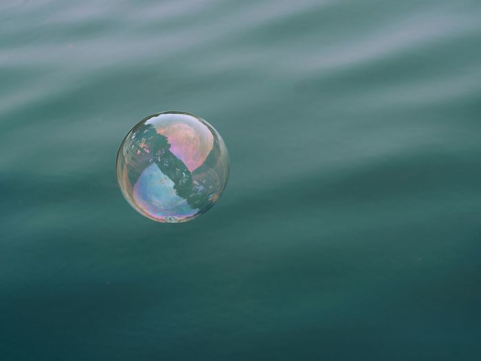 Close-up of soap sud bubble flying over water